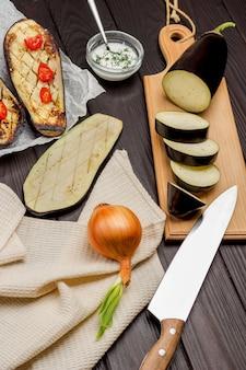 Berinjela crua picada e faca de cozinha na tábua de cortar berinjela assada no papel cebola e guardanapo bege