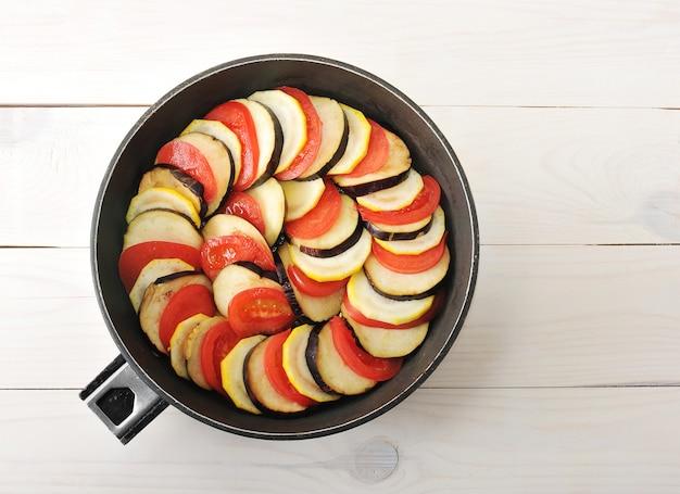 Berinjela crua, tomate e abobrinha cortada em fatias em uma frigideira funda.