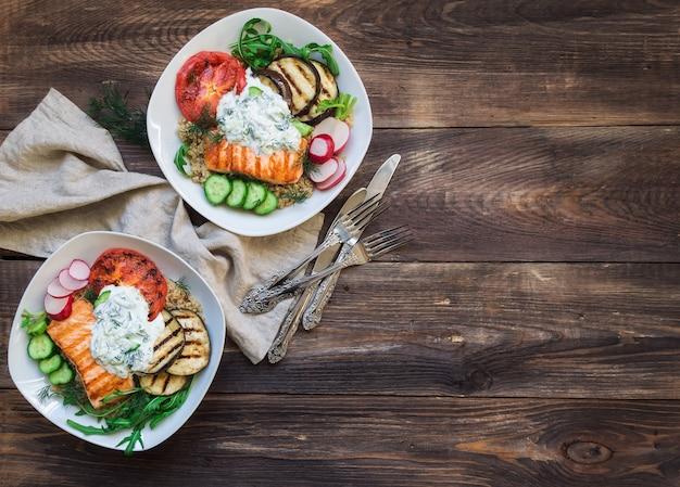 Berinjela de salmão grelhado e tomate com molho de quinua e tzatziki em fundo de madeira rústico