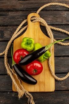 Berinjela de tomate fresco maduro vermelho de legumes frescos e pimentão verde em uma mesa rústica marrom