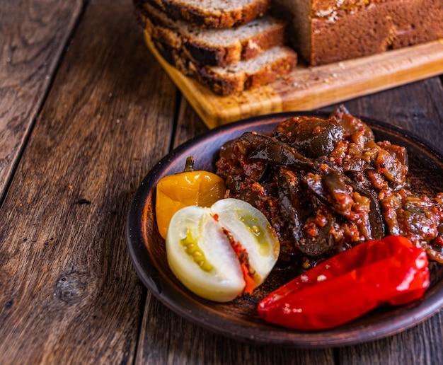 Berinjela em conserva tomate pepino e pimenta em faiança sobre uma mesa de madeira picles caseiros