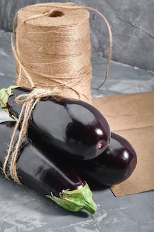 Berinjela em um fundo cinza, atrás de sacos de papel e urze para embalagem. entrega de vegetais, foto para lojas online com entrega.