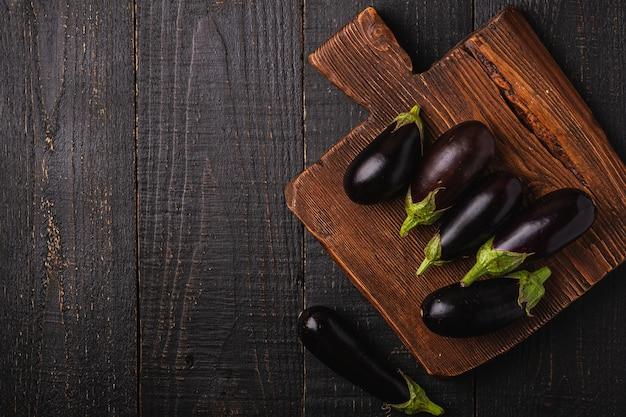 Berinjela fresca e madura em uma tábua de madeira marrom