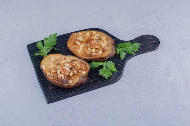 Berinjela frita com folhas de salsa em uma placa de madeira com fundo de mármore.