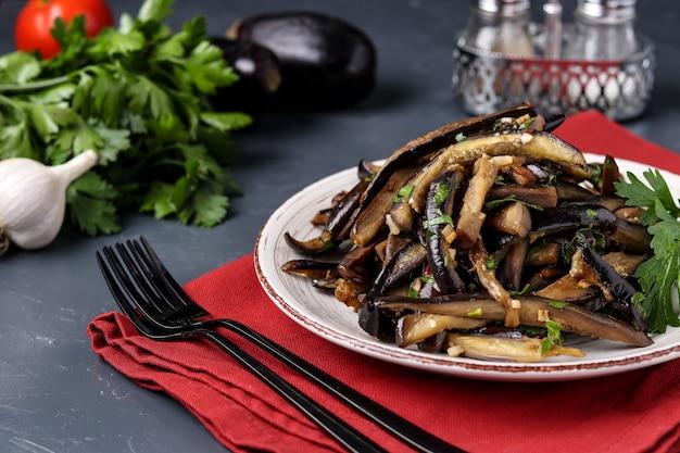 Berinjela frita com molho de alho e soja, fatiada em listras, em um prato contra um escuro
