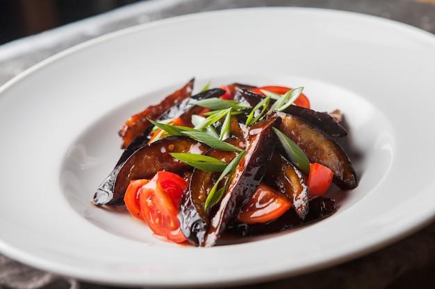 Berinjela frita de vista lateral com tomate e cebolinha picada e pano no prato branco redondo
