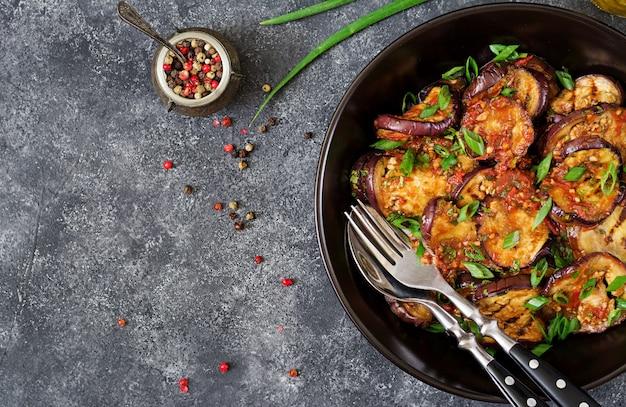 Berinjela grelhada com molho de tomate, alho, coentro e hortelã. comida vegana. beringela grelhada. vista do topo. configuração plana