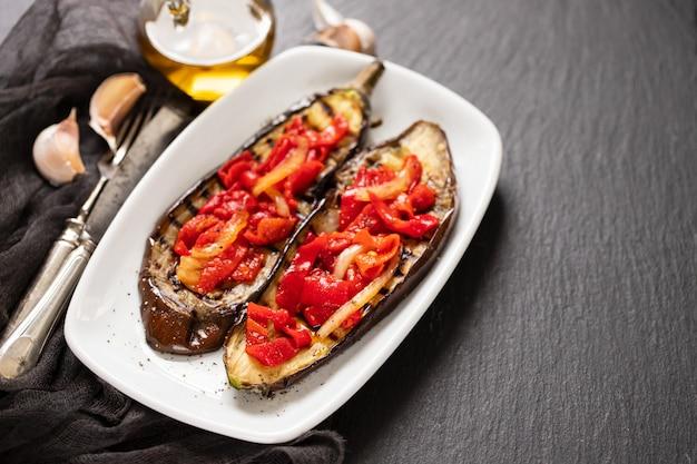 Berinjela grelhada com pimenta vermelha em prato branco