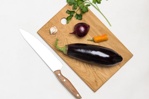 Berinjela inteira crua e cebola na tábua de cortar faca de cozinha e raminho de salsa na mesa