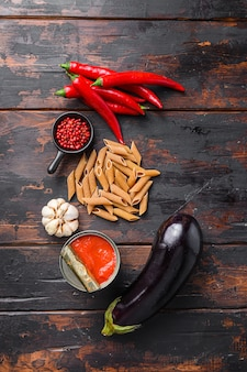 Berinjela penne ingredientes e macarrão de berinjela na velha mesa de madeira