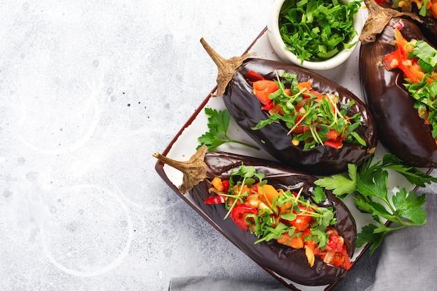 Berinjela recheada assada com diferentes vegetais, tomate, pimenta, cebola e salsa em pedra cinza ou fundo de mesa de concreto. vista do topo