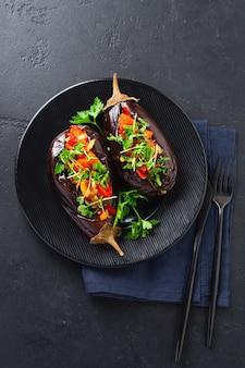 Berinjela recheada assada com diferentes vegetais, tomate, pimenta, cebola e salsa em uma pedra preta ou fundo de mesa de concreto. vista do topo
