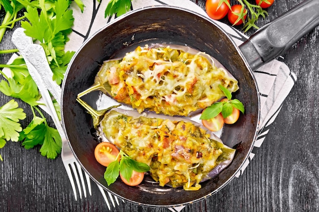 Berinjela recheada com peito defumado, tomate, cebola, cenoura com alho, queijo e ervas em uma panela em um guardanapo no fundo da placa de madeira de cima