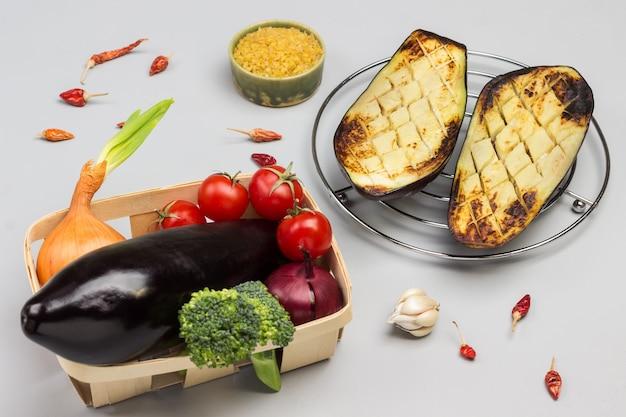 Berinjelas assadas em uma grade de metal berinjela crua com legumes na cesta