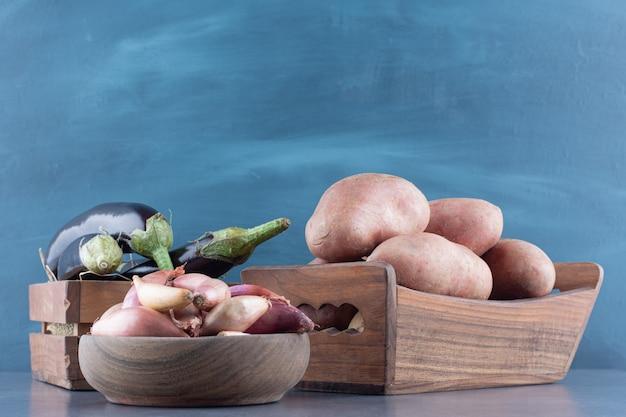 Berinjelas, batatas e cebolas em caixas de madeira.