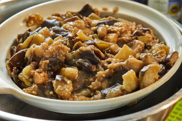Berinjelas fritas no forno colocam-se na peneira em uma tigela. fechar-se