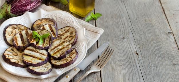 Berinjelas grelhadas temperadas com azeite de oliva fechadas em uma mesa de madeira com espaço de cópia