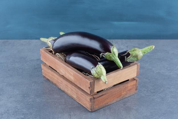 Berinjelas maduras frescas em caixa de madeira. Foto gratuita