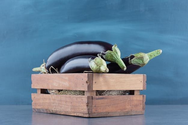 Berinjelas maduras frescas em caixa de madeira.