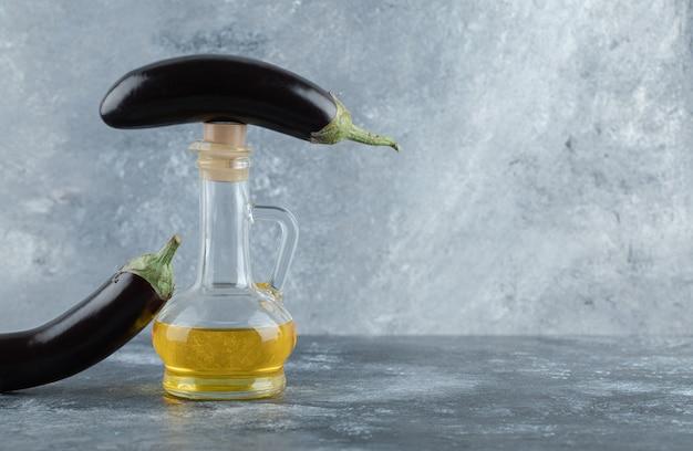 Berinjelas orgânicas frescas com garrafa de óleo.