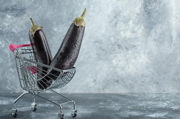 Berinjelas roxas maduras em um pequeno carrinho de compras