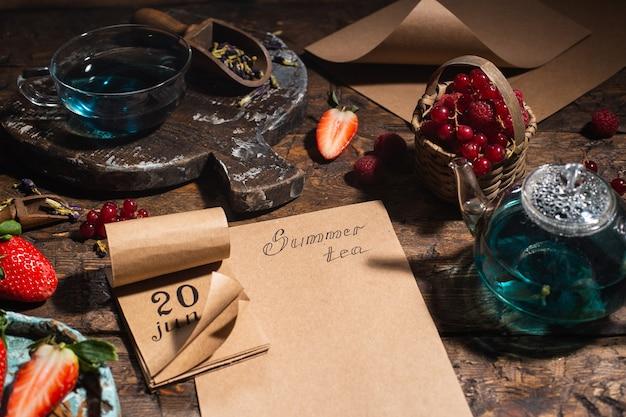 Berry ainda vida. bagas, chá, caneta, calendário, caderno em uma velha mesa de madeira marrom, vista superior