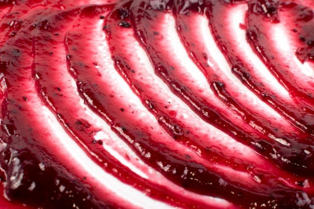 Berry jam vermelho escuro espalhado no fundo liso ou