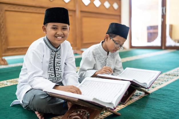 Bestfriend asiático muçulmano da criança que lê quran