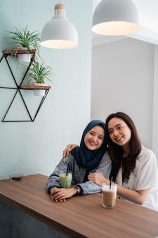 Bestfriend muçulmano asiático da mulher junto no café