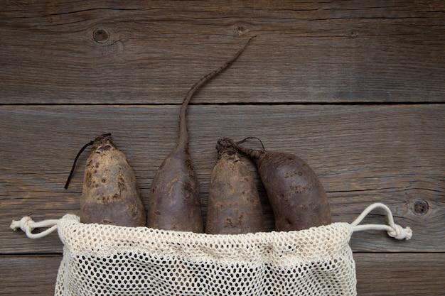 Beterraba orgânica alongada encontra-se em um saco de algodão em uma mesa de madeira.