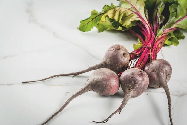 Beterrabas cruas do fazendeiro orgânico fresco com folhas em uma mesa de cozinha de mármore branca.