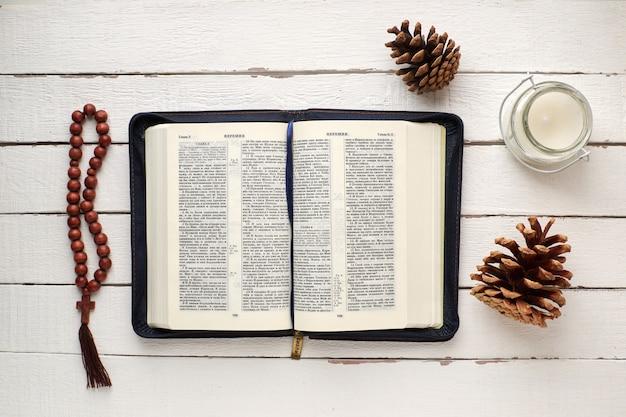 Bíblia aberta com rosário, uma vela e pinhas em uma mesa de madeira branca