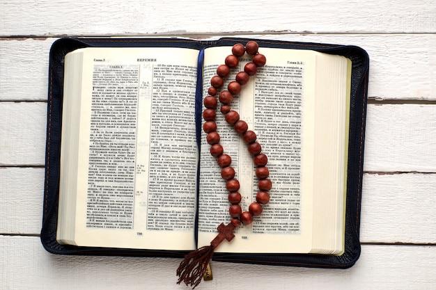 Bíblia aberta e rosário em uma mesa de madeira branca