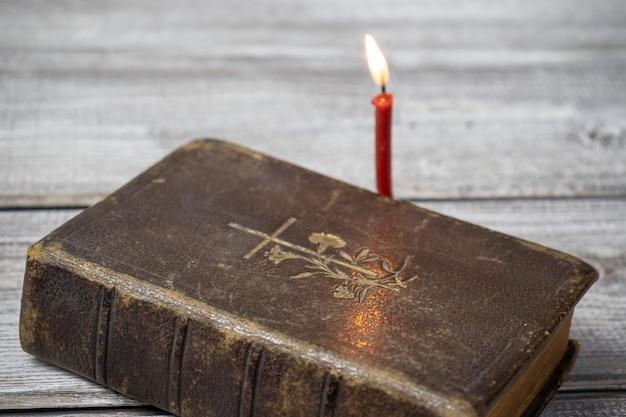 Bíblia católica e igreja vermelha queimando vela no fundo de madeira