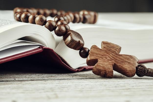 Bíblia e um crucifixo em uma velha mesa de madeira. conceito de religião.