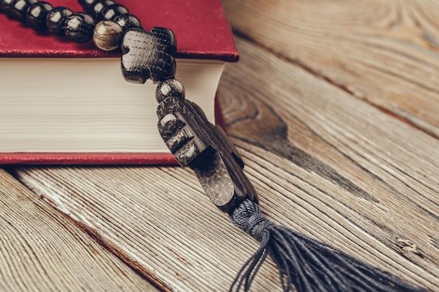 Bíblia e um crucifixo em uma velha mesa de madeira. religião.