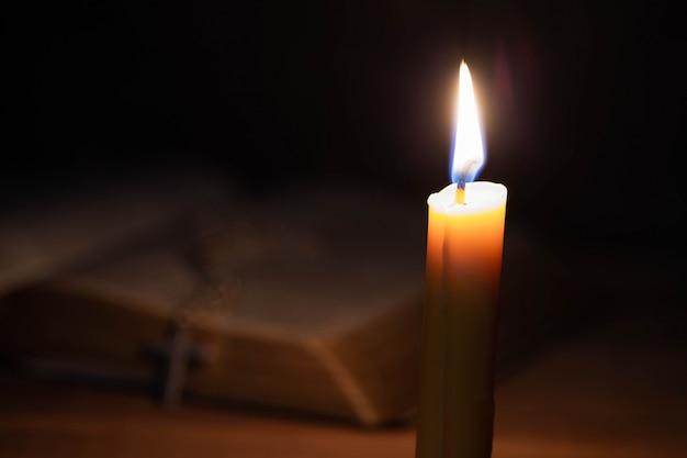 Bíblia e vela em uma velha mesa de madeira de carvalho.