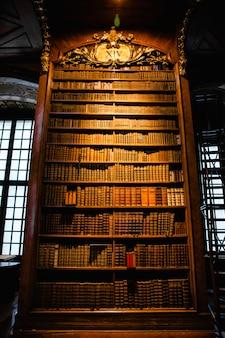 Biblioteca antiga, pouco iluminada e dourada