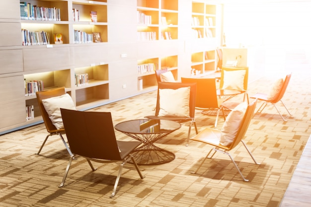Biblioteca em casa com estantes com cadeiras perto dela.
