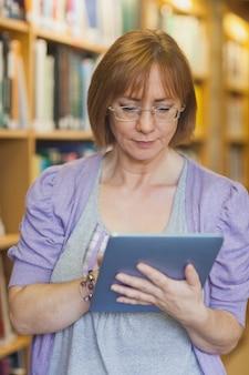 Bibliotecária feminina usando concentrou seu tablet