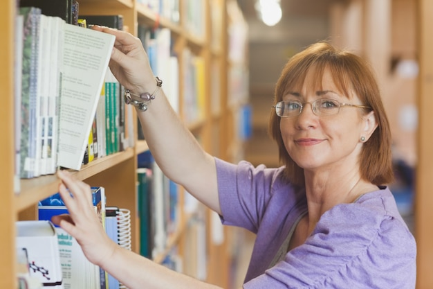 Bibliotecário feminino maduro, tirando um livro de uma prateleira