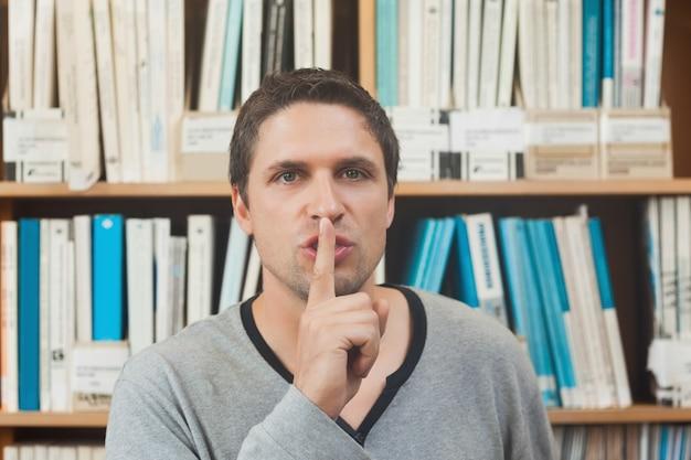 Bibliotecário masculino moreno que pede silêncio na biblioteca