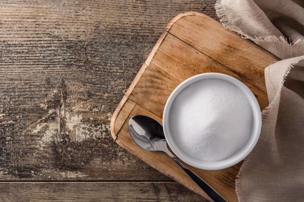 Bicarbonato de sódio em uma tigela branca na mesa de madeira vista superior copyspace