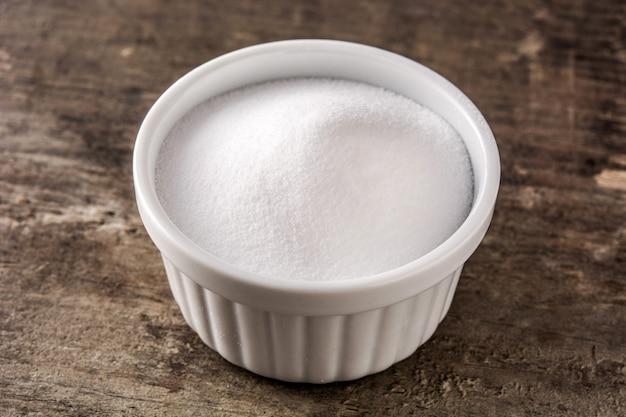 Bicarbonato de sódio em uma tigela branca na mesa de madeira.