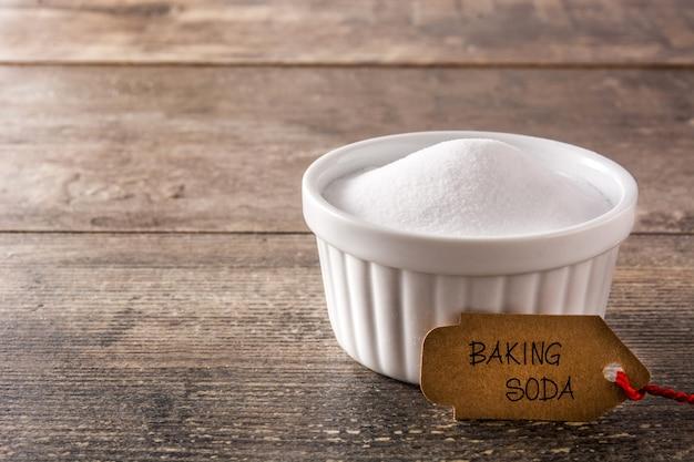 Bicarbonato de sódio em uma tigela branca na mesa de madeira