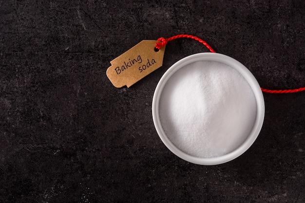 Bicarbonato de sódio na bacia branca na opinião superior do fundo preto. copie o espaço