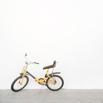 Bicicleta amarela estacionada em frente a parede branca
