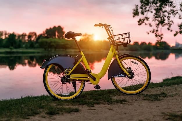 Bicicleta amarela no lago. céu rosa pôr do sol