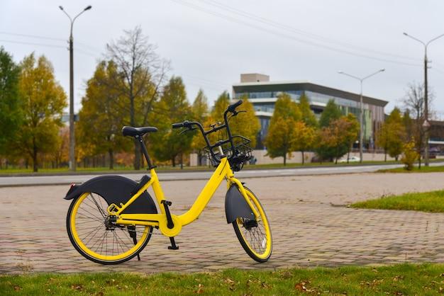 Bicicleta amarela para compartilhamento está de pé perto de uma estrada na cidade