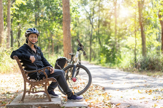 Bicicleta asiática sênior da mulher com sentado no parque